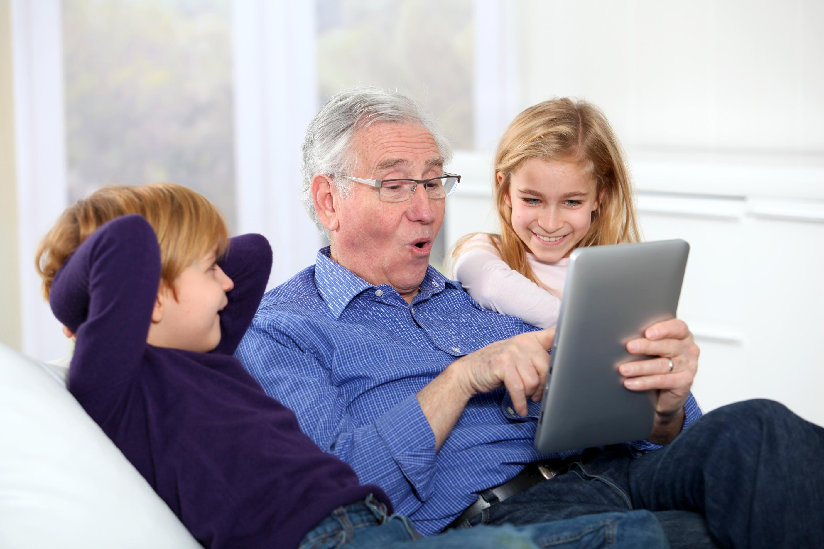 Grandfather sitting with grandchildren using a tablet